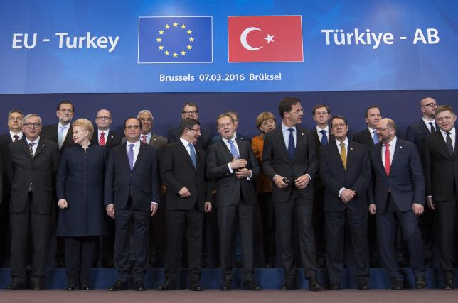 Turkish Prime Minister Ahmet Davutoglu (C) poses with European Union leaders during a EU-Turkey summit in Brussels, as the bloc is looking to Ankara to help it curb the influx of refugees and migrants flowing into Europe, March 7, 2016. REUTERS/Yves Herman