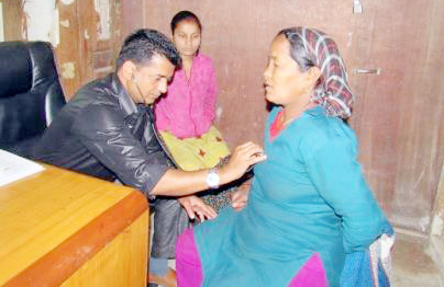 Gynaecologist Dr Rajan Neupane checking a patient in District Hospital, Bajura, on Monday, March 28, 2016. Photo: THT
