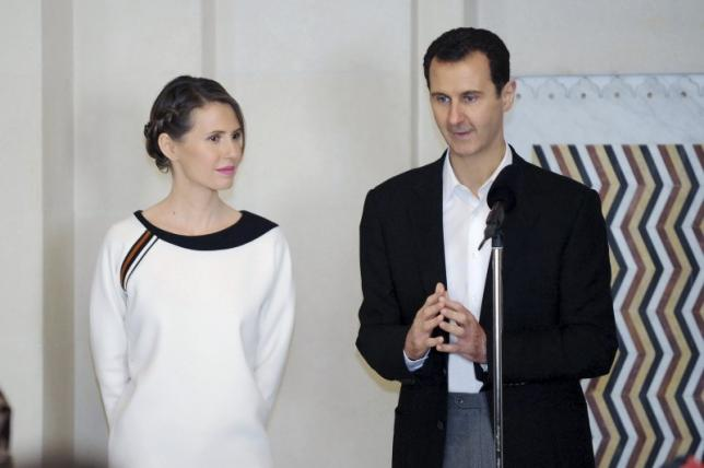 Syria's President Bashar al-Assad stands next to his wife Asma, as he addresses injured soldiers and their mothers during a celebration marking Syrian Mother's Day in Damascus, in this handout picture provided by SANA on March 21, 2016. REUTERS/SANA/Handout via Reuters