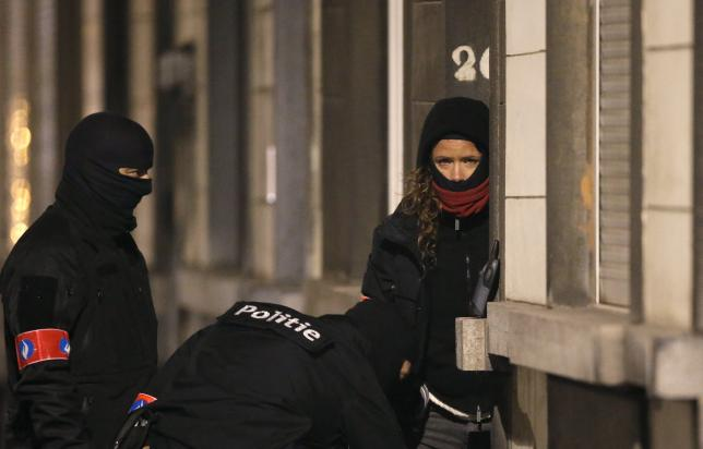 Masked Belgian police secure the entrance to a building in Schaerbeek during police operations following Tuesday's bomb attacks in Brussels, Belgium, March 25, 2016. REUTERS/Christian Hartmann