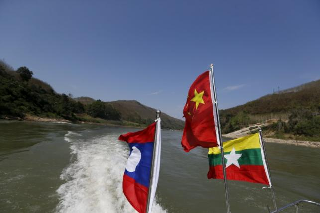 Flags flutter on a boat while a delegates from China's Narcotics Control Bureau, the United Nations Office on Drugs and Crime (UNODC), Laos, Myanmar and Thailand travel on an inspection trip on the Mekong river near the border between China, Laos and Myanmar March 1, 2016. REUTERS/Jorge Silva