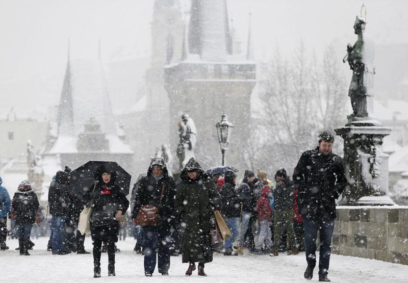 People cross the Charles Bridge as snow falls in Prague, Czech Republic, on Wednesday, February 17, 2016. Photo: AP