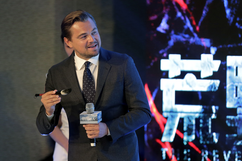 Actor Leonardo DiCaprio holds a Chinese writing brush as he prepares to write his name on stage during a news conference of the movie u0093The Revenantu0094 at a hotel in Beijing, Sunday, March 20, 2016. Photo: AP