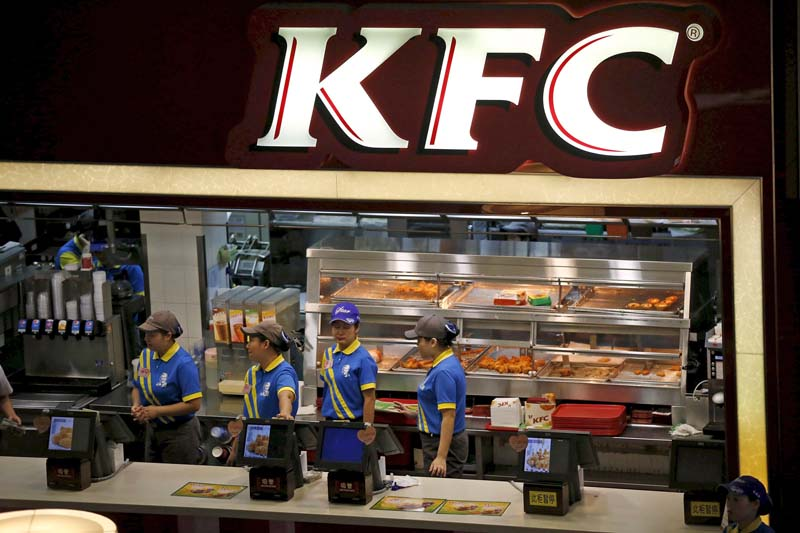 Employees work at a KFC store, owned by the Yum Brands Inc in Shanghai on July 29, 2014. Photo: Reuters/ File