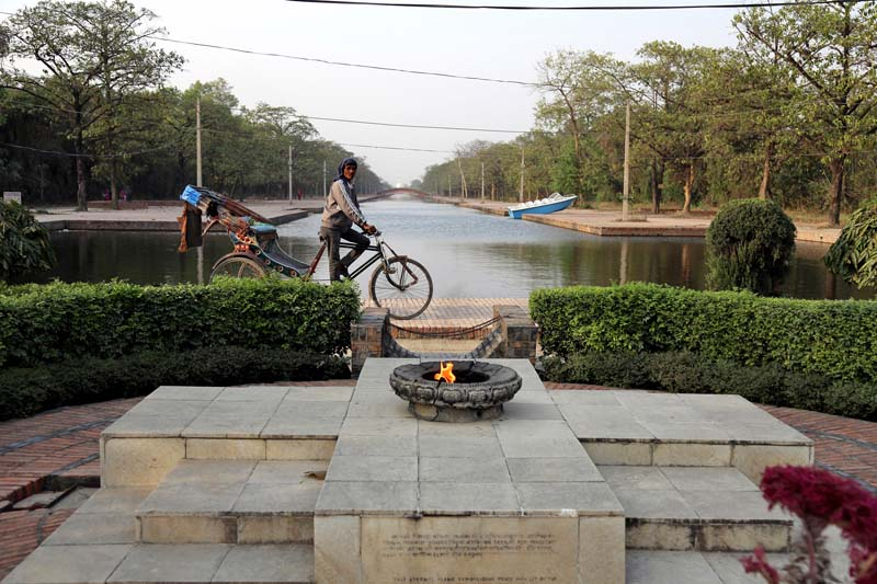 A rickshaw puller passes by the Eternal Peace Flame in the premises of the Mayadevi Temple, in Lumbini, the birthplace of Gautam Buddha, on Thursday, March 17, 2016. Photo: RSS