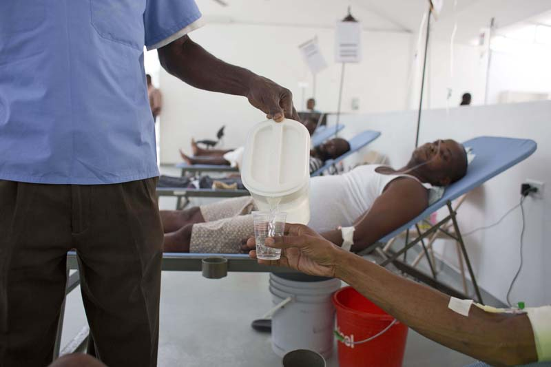 A worker pours water for a patient at Haiti's first permanent cholera center, run by Gheskio Centers, in downtown Port-au-Prince, Haiti on February 24, 2016. Photo: AP