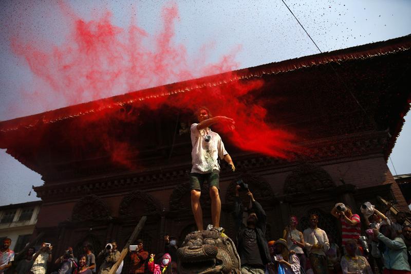A man throws coloured vermilion powder during celebrations of Holi festival, at Basantapur Durbar Square in Kathmandu, on Tuesday, March 22, 2016. Photo: Skanda Gautam