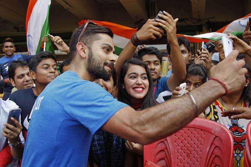 India's Virat Kohli takes a selfie with his fans after participating in a training session ahead of their ICC World Twenty20 2016 match against Bangladesh in Bangalore, India, on Tuesday, March 22, 2016. Photo: AP
