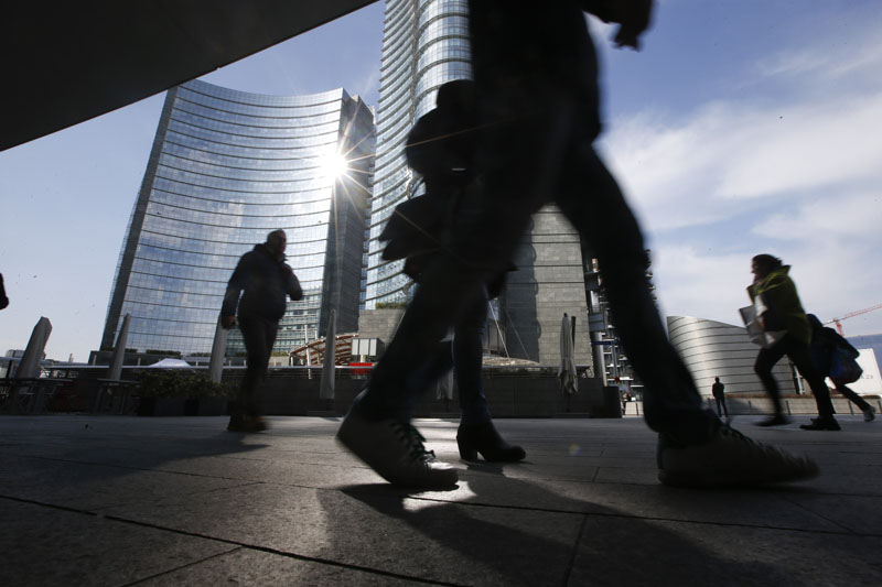 People walk in the Porta Nuova business center in Milan, Italy, on Friday, March 11, 2016.  Photo: AP