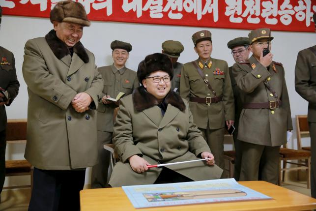 North Korean leader Kim Jong Un (seated) smiles during a solid-fuel rocket engine test in this undated photo released by North Korea's Korean Central News Agency (KCNA) in Pyongyang March 24, 2016. REUTERS/KCNA