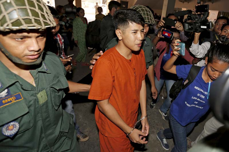Kong Raya (centre), is escorted by police officers as he arrives the Municipal Court of Phnom Penh on March 15, 2016. Photo: Reuters