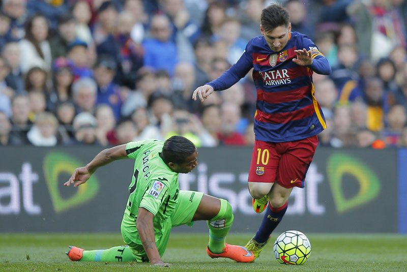 FC Barcelona's Lionel Messi (right) duels for the ball against Getafe's Alvaro Pereira during a Spanish La Liga soccer match at the Camp Nou stadium in Barcelona, Spain, on Saturday, March 12, 2016. Photo: AP