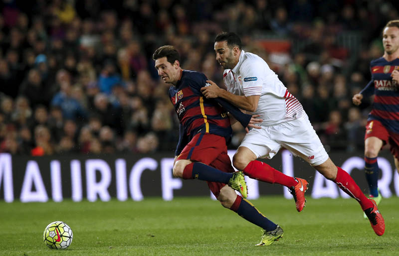 Barcelona's Lionel Messi (left) and Sevilla's Adil Rami vie for the ball during their Spanish League match at the Camp Nou Stadium in Barcelona on Sunday. Photo: Reuters