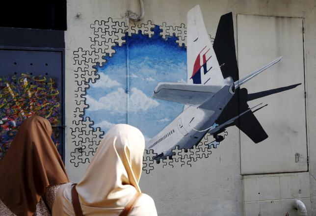Women look at a mural of missing Malaysia Airlines flight MH370 two years after it disappeared, in Kuala Lumpur, Malaysia, March 7, 2016. REUTERS/Olivia Harris