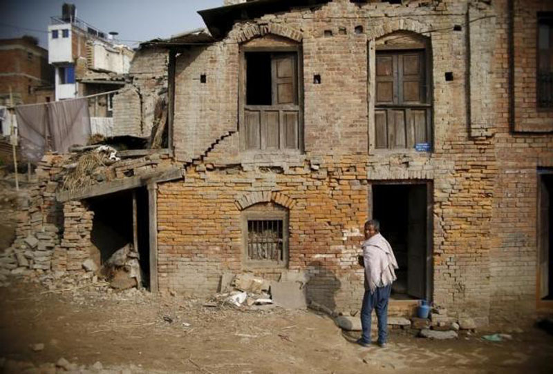 A man stands outside his house, which was damaged during last year's earthquake, in Bhaktapur, Nepal, January 29, 2016.  Photoi: Reuters