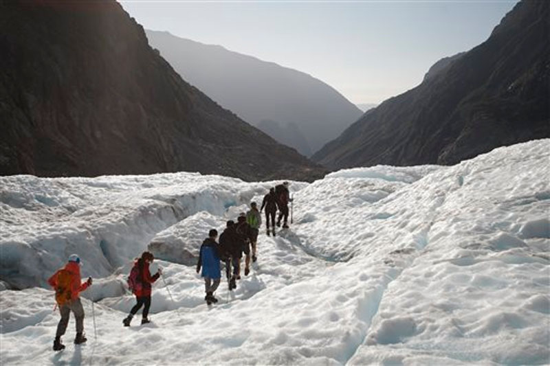 Tourists who have taken a helicopter trip onto the Fox Glacier follow a guide in New Zealand, on February 6, 2016. Photo: AP