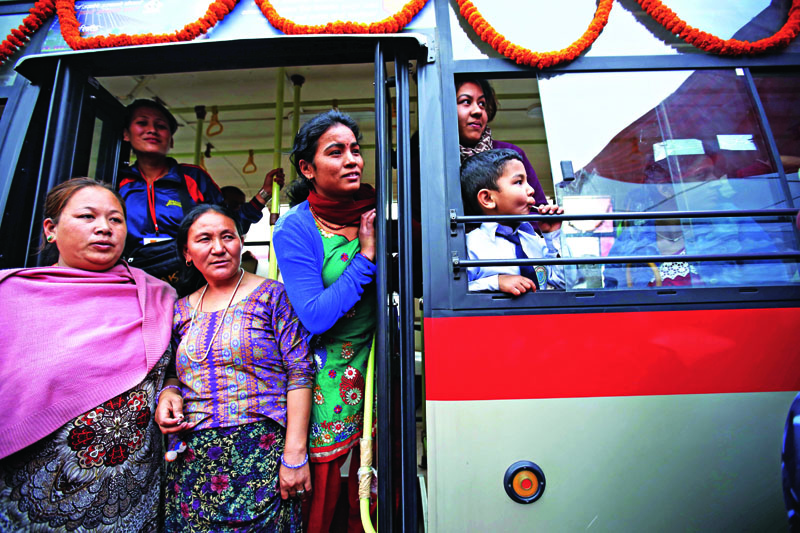 People glance from a new metro public bus in Banasthali, Kathmandu on Sunday. A total of 39 new metro public buses introduced by a private company are to be operated along the Ring Road. Photo: Skanda Gautam/THT