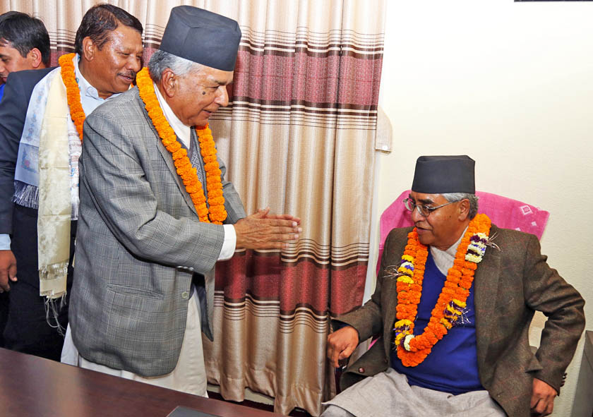 Outgoing Acting President Ram Chandra Paudel greets Nepali Congress President Sher Bahadur Deuba after handing over the leadership at the Nepali Congress central office in Sanepa on Wednesday, March 16, 2016. Outgoing General Secretary Prakash Man Singh is also seen on the backdrop. Photo: RSS