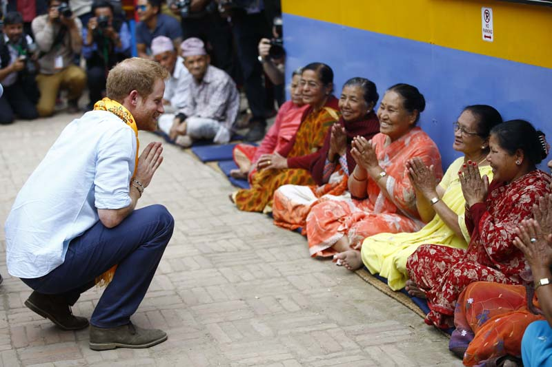 Prince Harry gestures to local elderly citizens inside the Golden Temple premises near historic the Patan Durbar Square, a UNESCO World heritage site in Lalitpur, on Sunday, March 20, 2016. Photo: Skanda Gautam/ THT