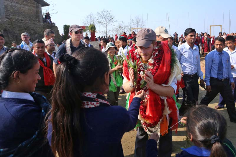 Britain's Prince Harry accepts flowers and blessings from locals and school children in Gainda VDC of Lamjung