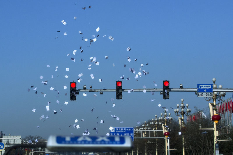 Protest flyers thrown by petitioners are tossed up over the traffic lights at a junction near Tiananmen Square during a plenary session of the National People's Congress at the Great Hall of the People in Beijing, on Monday, March 7, 2016. Photo: AP