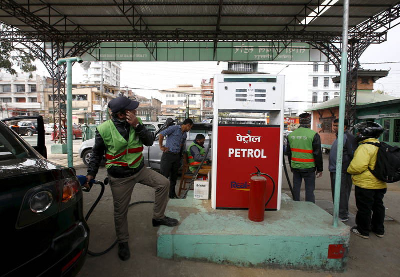 A petrol pump attendant (L) puts petrol priced at Rs 99 per litre into a car at a Sajha Petrol gas station in Kathmandu, Nepal, January 27, 2016. A dramatic drop in oil prices, driven down by a glut in supply, is translating into a mixed bag for motorists. All countries have access to the same oil prices on international markets, but retail prices vary wildly, largely because of taxes and subsidies. Reuters