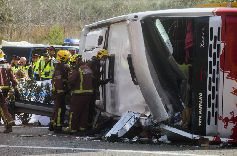 Emergency services personnel stand at the scene of a bus accident crashed on the AP7 highway that links Spain with France along the Mediterranean coast near Freginals halfway between Valencia and Barcelona, early on Sunday, March 20, 2016. Photo: AP