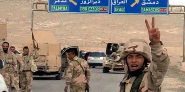 Forces loyal to Syria's President Bashar al-Assad gesture as they advance into the historic city of Palmyra in this picture provided by SANA on March 24, 2016. REUTERS/SANA/Handout via Reuters