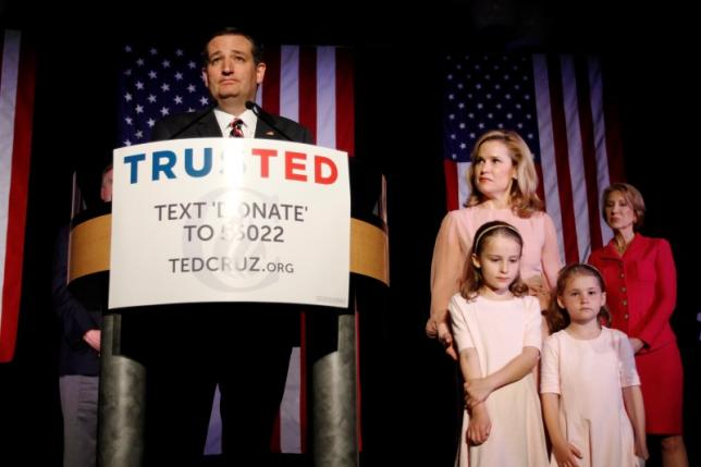 Republican presidential candidate Senator Ted Cruz, with his daughter Catherine (2nd L), wife Heidi (C), daughter Caroline (2nd R) and supporter and former rival Carly Fiorina (R) at his side, reacts to the primary election results in Florida, Ohio and Illinois during a campaign rally in Houston, Texas March 15, 2016. REUTERS/Trish Badger