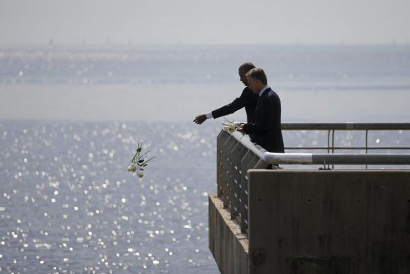 US President Barack Obama throws flowers in the River Plate while visiting with Argentina's President Mauricio Macri (R) at the Parque de la Memoria (Remembrance Park) where they honored victims of Argentina's Dirty War on the 40th anniversary of the 1976 coup that...nReuters/Carlos Barrian