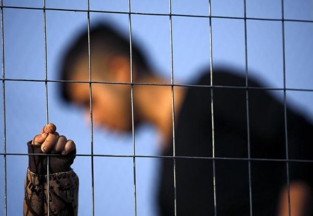 An Afghan child holds onto a metal fence at a temporary UNHCR camp on the Greek island of Lesbos October 20, 2015. REUTERS/Yannis Behrakis