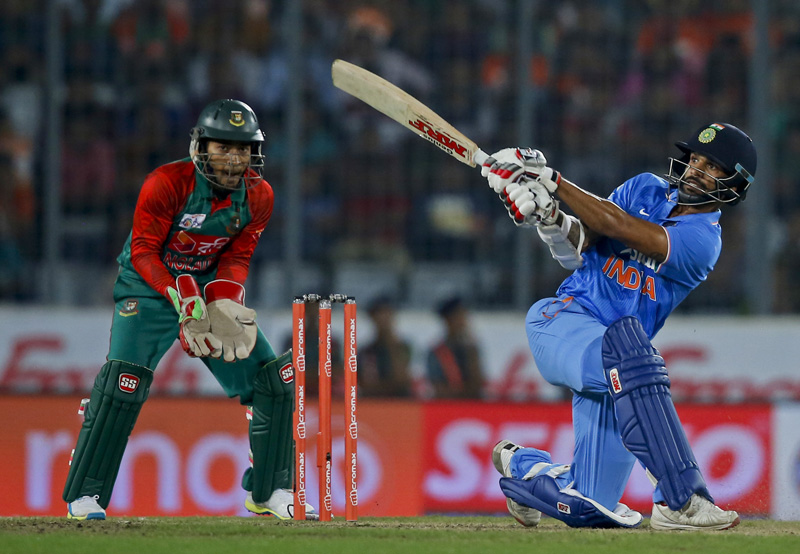 Indiau0092s Shikhar Dhawan plays a shot, as Bangladeshu0092s wicketkeeper Mushfiqur Rahim follows the ball during the Asia Cup Twenty20 international cricket final match between them in Dhaka, Bangladesh, Sunday, March 6, 2016. Photo: AP