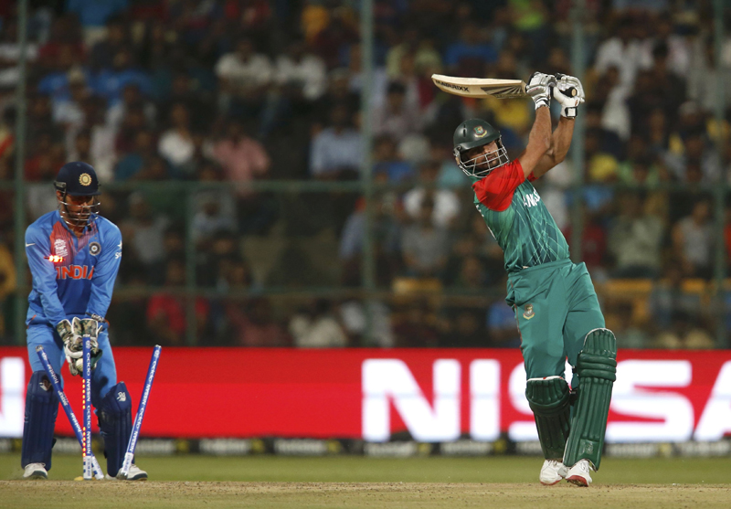 Bangaldes's Mashrafe Mortaza (R) is bowled as India's captain and wicketkeeper Mahendra Singh Dhoni looks on during ICC World Twenty20 Cricket tournament in Banglore on Wednesday, March 23, 2016. Photo: Reuters