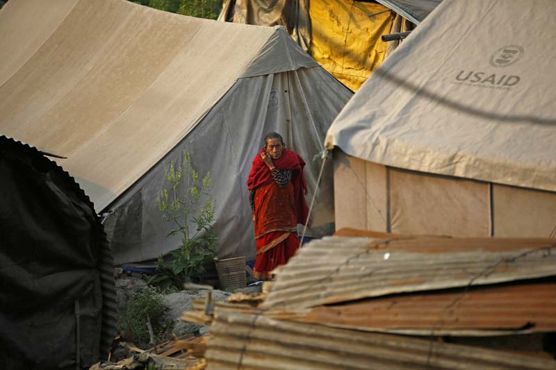 An elderly citizen walks past makeshift tents before Prince Harry's arrival to visit earthquake survivors, residing in makeshift tents displaced by the earthquakes that occurred last year, in Byasi, Bhaktapur, on Sunday, March 20, 2016. Photo: Skanda Gautam/ THT