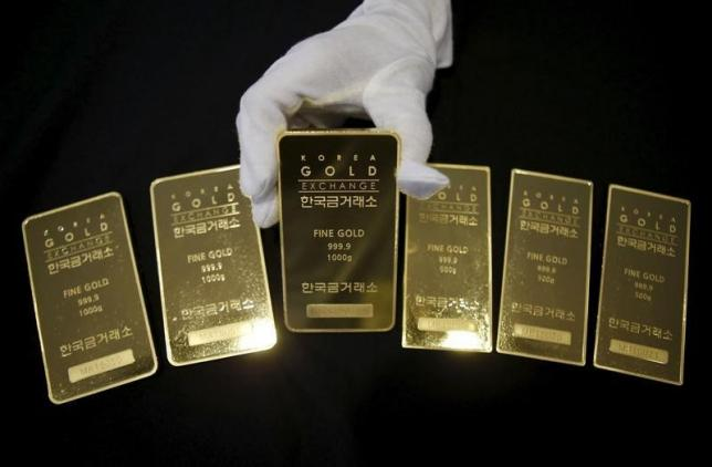 An employee poses for photographs with gold bars at the Korea Gold Exchange in Seoul, South Korea, July 31, 2015.   REUTERS/Kim Hong-Ji