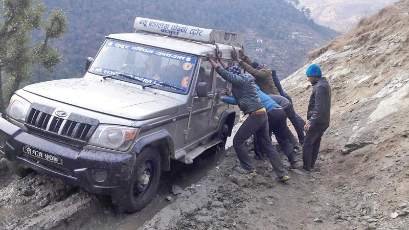 People trying to take a jeep out of mud along the Martadi-Kolti road section in Bajura district. Photo: Prakash Singh