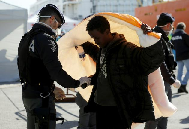 A migrant is inspected by policemen after disembarking from the Norwegian vessel Siem Pilot at Pozzallo's harbour, Italy, March 29, 2016.   REUTERS/Antonio Parrinello