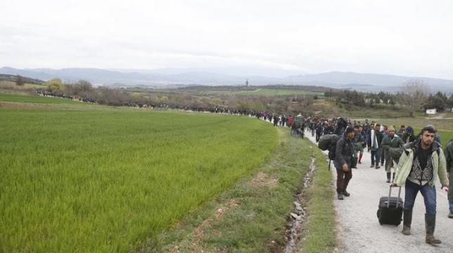 Migrants walk along a path looking for a way to cross the Greek-Macedonian border, near the village of Idomeni, Greece, March 14, 2016. REUTERS/Stoyan Nenov