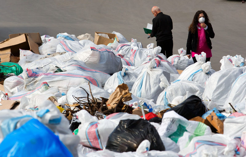 A Lebanese woman covers her mouth with a medical mask as she passes by a pile of garbage on a street in Beirut, Lebanon, on Friday, March 4, 2016. Photo: AP