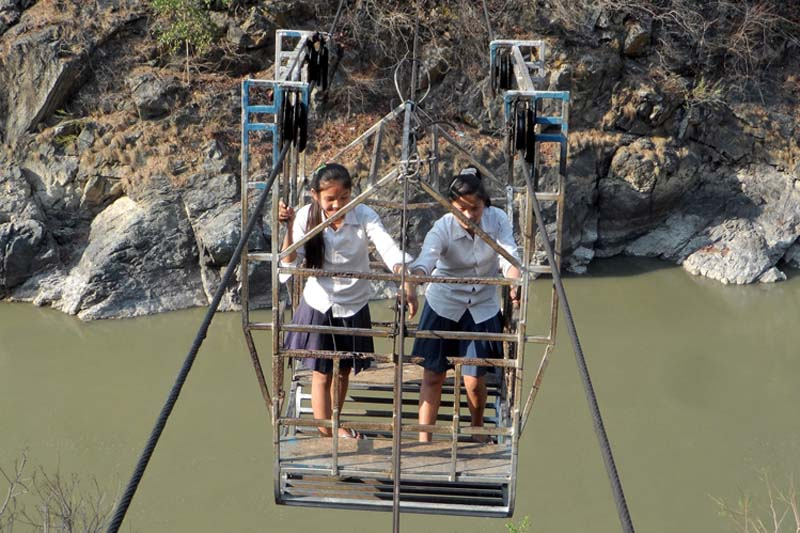 Local school girls crossing the Trishuli River using a ramshackle cable crossing (tuin) in order to appear in their examinations, in Tanglichok VDC of Gordi village, Gorkha, on Wednesday, March 30, 2016. Photo: RSS