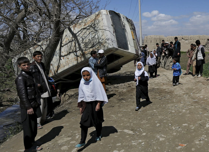 Schoolgirls walk past a damaged mini-bus after it was hit by a bomb blast in the Bagrami district of Kabul, Afghanistan, on April 11, 2016.  Photo: Mohammad Ismail/Reuters