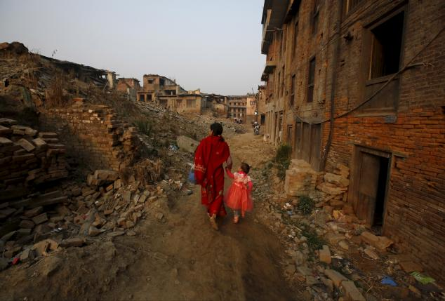 A woman and a child walk past the remains of collapsed houses damaged during the April 2015 earthquake, in Bhaktapur, Nepal March 18, 2016. REUTERS/Navesh Chitrakar