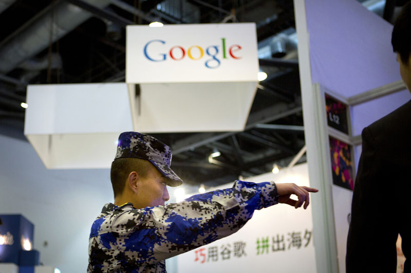 FILE - A security guard points while walking past a display booth for Google at the Global Mobile Internet Conference in Beijing, on April 29, 2015. Photo: AP
