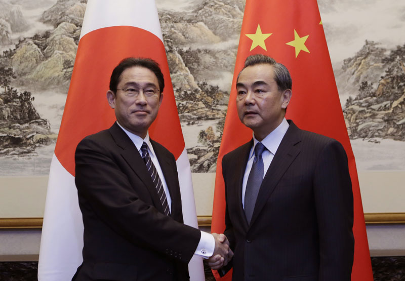 Japanese Foreign Minister Fumio Kishida (left) shakes hands with China's Foreign Minister Wang Yi during a meeting at Diaoyutai State Guesthouse, in Beijing, China, on Saturday, April 30, 2016. Photo: Jason Lee/Pool Photo via AP