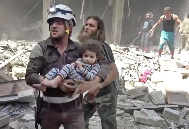A Civil Defence worker carries a child after airstrikes hit Aleppo, Syria, on Thursday, April 28, 2016. Photo: Validated UGC via AP video