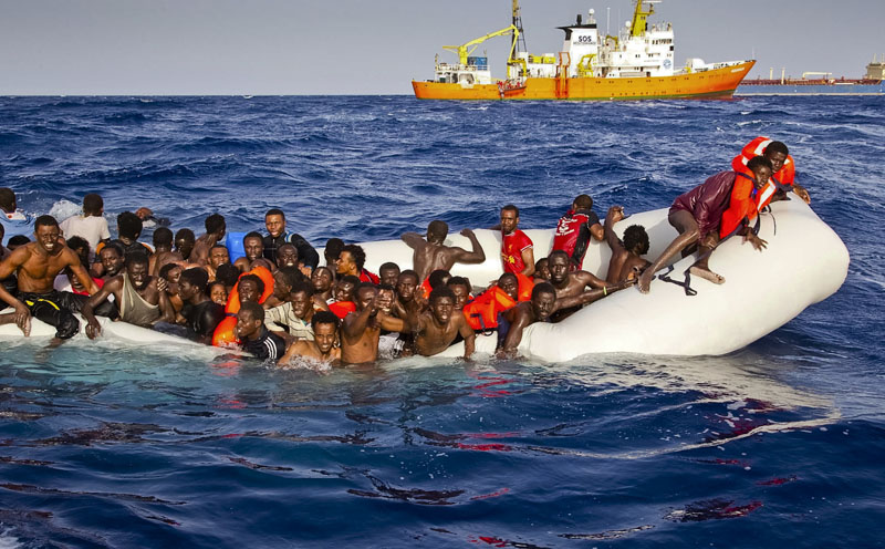Migrants ask for help from a dinghy boat as they are approached by the SOS Mediterranee's ship Aquarius, background, off the coast of the Italian island of Lampedusa, on Sunday, April 17, 2016. Photo: Patrick Bar/SOS Mediterranee via AP