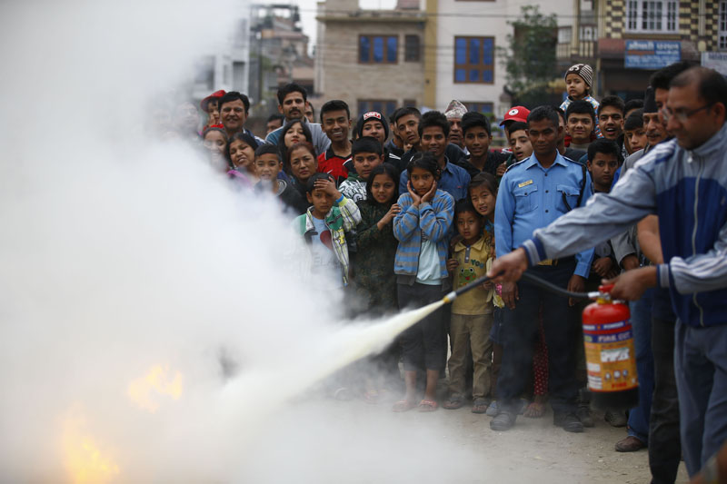 A man learns to use a canister to douse fire. Photo: Skanda Gautam/THT