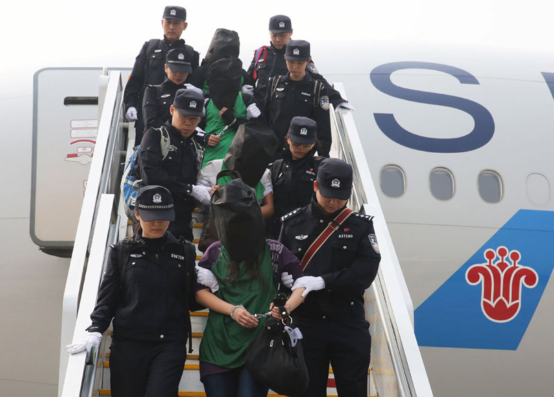 Police escort a group of people wanted for suspected fraud in China, after they were deported from Kenya, as they get off a plane after arriving at Beijing Capital International Airport in Beijing, China, on Wdnesday, April 13, 2016. Photo: Yin Gang/Xinhua via Reuters