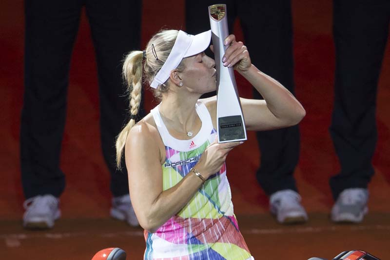 Germany's Angelique Kerber kisses the trophy in a Porsche 718 Boxster Cabrio, the winner's prize, after defeating Germany's Laura Siegemund (unseen) in the final of the WTA Porsche Tennis Grand Prix in Stuttgart, southwestern Germany, on April 24, 2016. Kerber won 6-4, 6-0. Photo: AFP