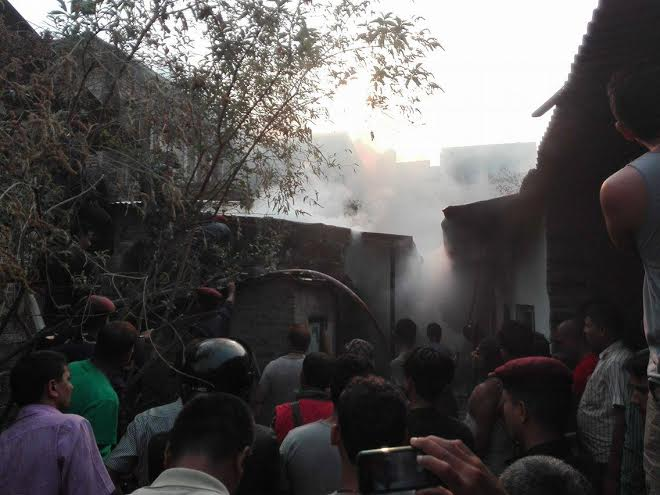 Locals and police personnel try to douse the fire that broke out at the Gautam Hardware in Mainroad of Hetaunda-10 on Thursday, April 21, 2016. Photo: Prakash Dahal